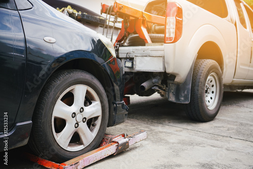 Tow truck picking up and towing old broken down car on a roadside Canvas Print