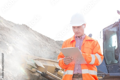 Engineer reading clipboard at construction site Fototapet