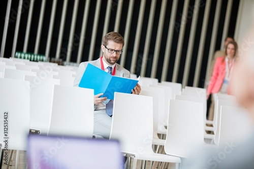 Valokuvatapetti Businessman reading file while sitting in seminar hall at convention center