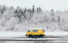Carpathians, Ukraine - December 2019: Yellow Camper Van With Winter Forest On Background