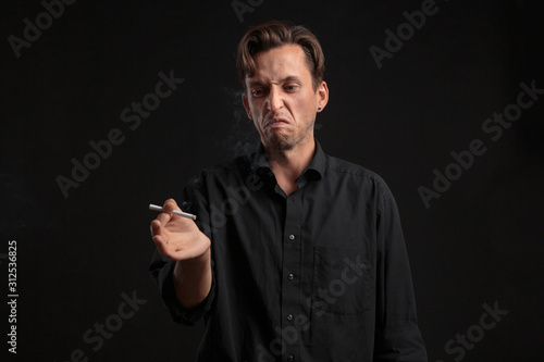 Young man looking with disgust at the cigarette over black background Wallpaper Mural