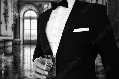 Photo A close up view of a man in a black tuxedo holding a whiskey glass in a mansion