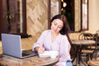 Smiling woman in cafe using laptop and note some data on notebook