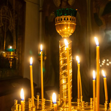 Wax Burning Candles In An Orthodox Church On The Dark Background. Religious Concept.