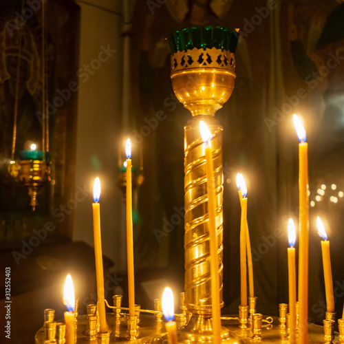 Wax burning candles in an orthodox church on the dark background Poster Mural XXL