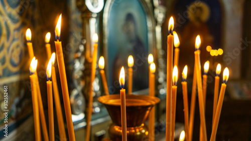 Foto Wax burning candles in an orthodox church on the blurred icon background
