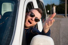 Young Man With Sunglasses Comes Out Of The Car Window With His Head With His Arm Raised. Face Expression Of Angry Driver Arguing And Gesturing. Express Courier With Work Vehicle. Negative Emotions.