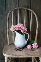 Roses In White Vase On Rustic Old Chair