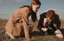 Twins Examining Ground In Field