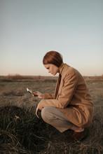 Young Woman Examining Dirt Pile