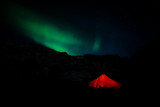 Red camping tent in night with north lights
