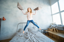 Cute Girl Jumping On The Bed, Happiness, Joyful And Throws A Pillow
