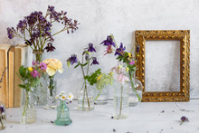 Old Books Cllse To A Collection Of Glass Vases With Water And Flowers And A Golden Framing