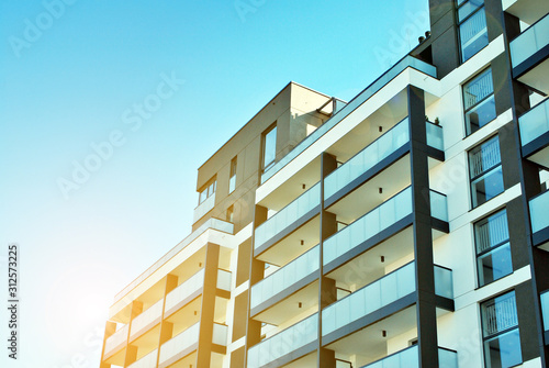 Fototapeta Sun rays light effects on urban buildings. Fragment of modern residential apartment with flat buildings exterior. Detail of new luxury house and home complex.  obraz