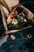 Hand Holding A Flower Bouquet On Table