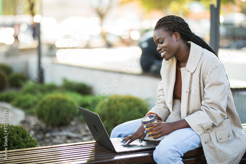 Fototapety, obrazy: Young african woman in park. Beautiful woman sitting on bench drinking coffee and using laptop via airpods.
