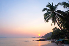 A Tropical Bay With A Calm Sea And Palm Trees Glowing Red In The Setting Sun, Panaji, Goa, India