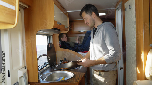 Vászonkép A man washes dishes in a motorhome. car travel concept