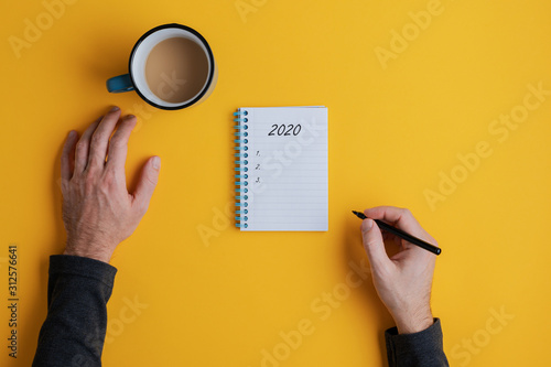 Fototapeta Top view of a man writing down plans or resolutions for the year 2020 obraz
