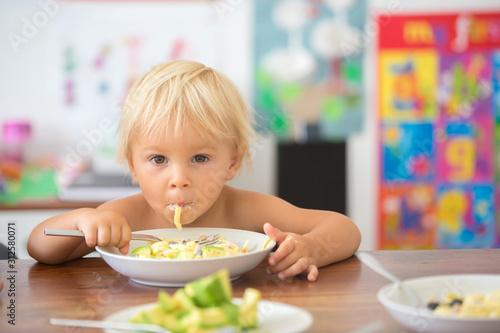 Cuadros en Lienzo  Sweet toddler boy, eating spaghetti at home, making a mess and having fun