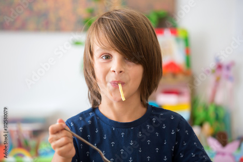 Fotografía  Sweet preschool boy, eating spaghetti at home, making a mess and having fun