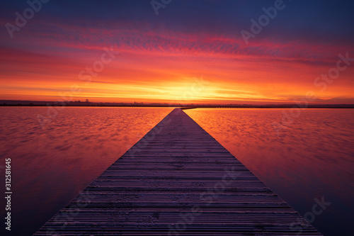 Foto  Very colorful and tranquil dawn at a jetty in a lake