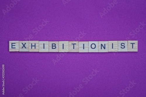 Fotografie, Obraz word exhibitionist from small gray wooden letters lies on a lilac background