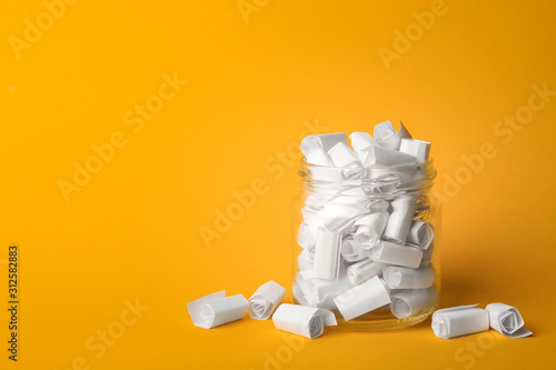 Stampa su Tela  Glass jar full of rolled paper sheets on yellow background, space for text