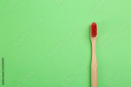 Obraz na plátně  Natural bamboo toothbrush on green background, top view