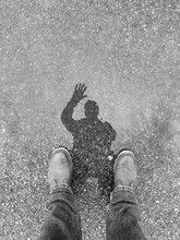 Man Waving Hello To Puddle And His Reflection In Silhouette Is Visible. Black And White.
