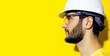 canvas print picture - Profile portrait of young bearded man wearing construction safety helmet and glasses on yellow background.