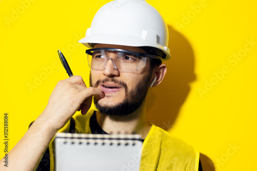 Fotomural  Studio portrait of a young thinking man, builder engineer wearing safety helmet and glasses for construction on yellow background