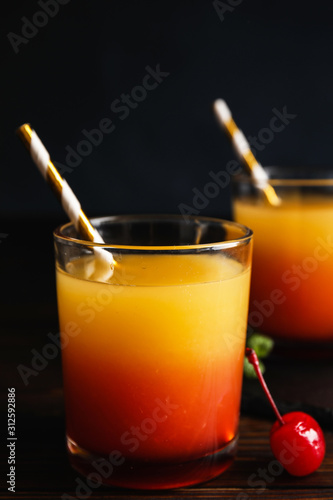 Cuadros en Lienzo  Fresh alcoholic Tequila Sunrise cocktail on wooden table