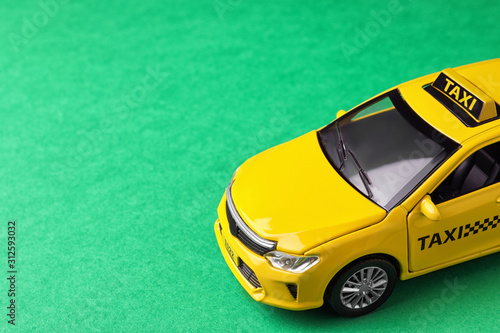 Yellow taxi car model on green background. Space for text Poster Mural XXL