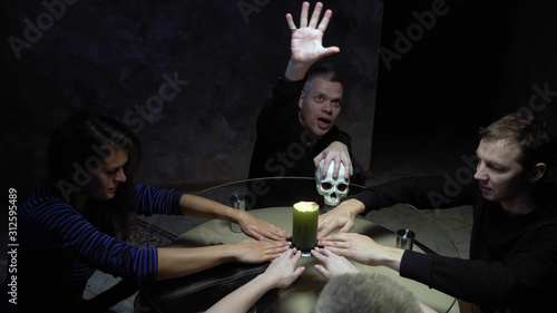A session of spiritualism group of people sitting at a round table holding hands Принти на полотні