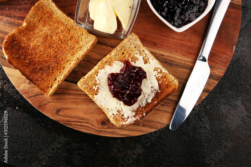 Leinwand Poster Toast bread with homemade strawberry jam and apricot marmalade on rustic table s