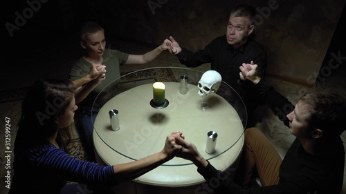 Fototapeta A session of spiritualism group of people sitting at a round table holding hands