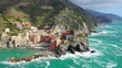A high altitude drone shot of Italy Cinque Terre with a mountain as background.