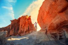 A Man Climbs On A Rock. Desert...