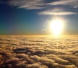canvas print picture - spectacular sunset seen from an airplane with clouds in the foreground,  blue sky and the sun in the distance