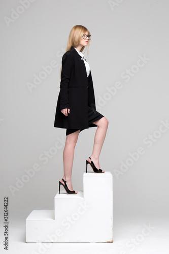 Obraz na plátně Blonde businesswoman stepping up a stairway concept