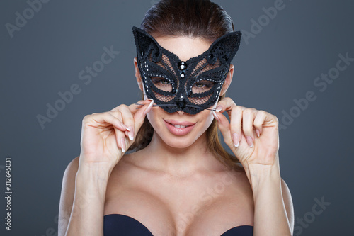 Canvas Print Sexy brunette woman holding mustache in catwoman mask