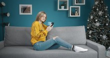 Young Beautiful Lady In Jeans And Hoodie Sitting On Couch With Cup Of Coffee And Texting On Smartphone Near Glowing Xmas Tree