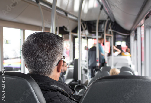 Rear view of man sitting in a seat on a public bus Canvas Print