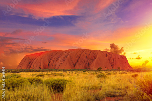 Fotografie, Obraz Colorful clouds at sunset sky over Ayers Rock in Uluru-Kata Tjuta National Park - at Living Cultural Landscape, Australia, Northern Territory