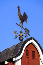 Copper Weathervane On Red Barn Cupola, Blue Sky Background.