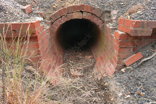 Fotografia, Obraz  red brick culvert drain under road