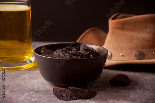 Fotografiet  Mexican corn chips nachos, glass of beer and cowboy hat