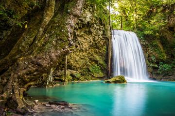 Fototapeta na wymiar Waterfall and blue emerald water color in Erawan national park. Erawan Waterfall Step 3rd Wang Na Pha , Beautiful nature rock waterfall steps in tropical rainforest at Kanchanaburi province, Thailand