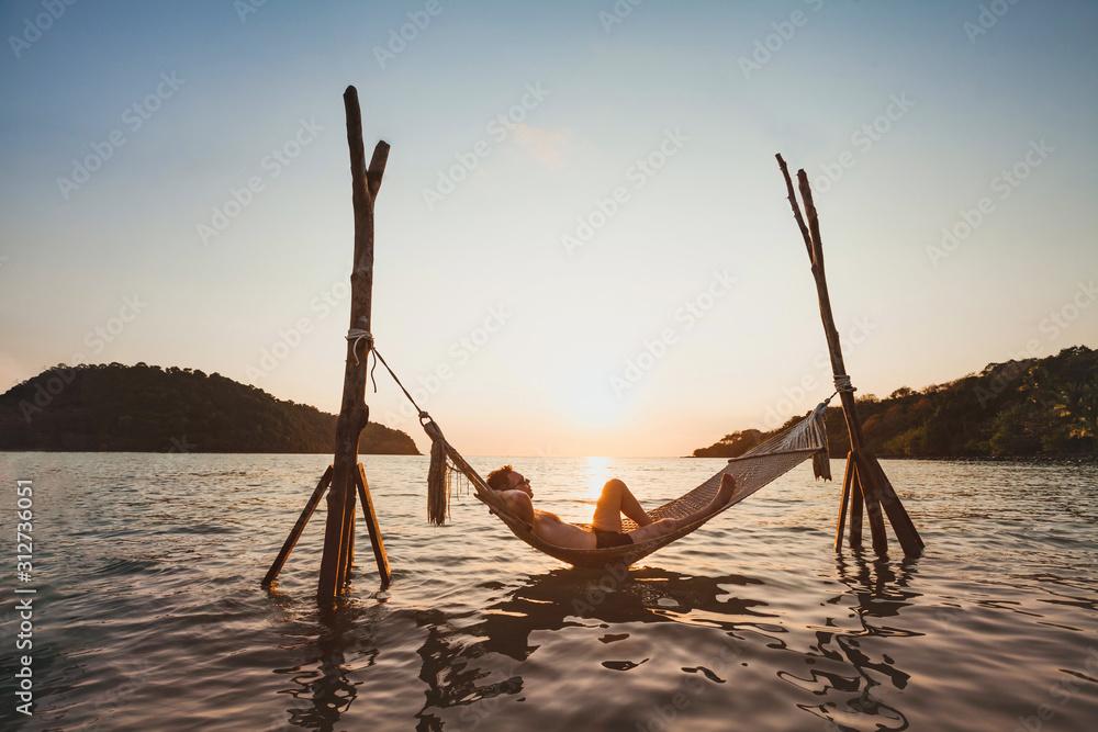 Fototapeta beach getaway, relaxation in hammock at sunset, paradise remote island holidays, happy man tourist resting and enjoying life